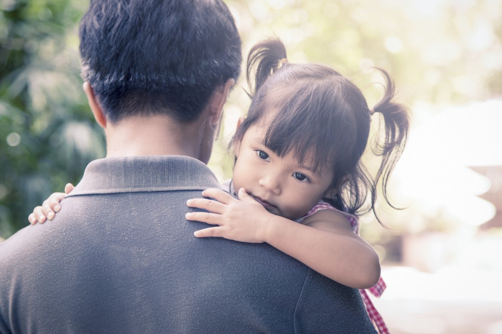 Father and child,cute little girl resting on her father's should