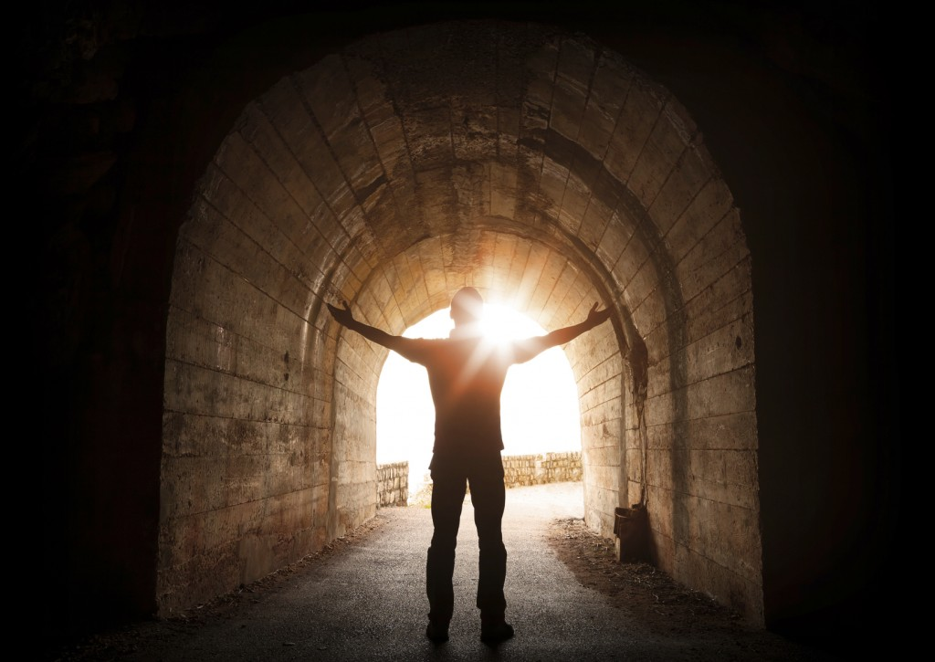 Man stands inside of old dark tunnel with shining sun