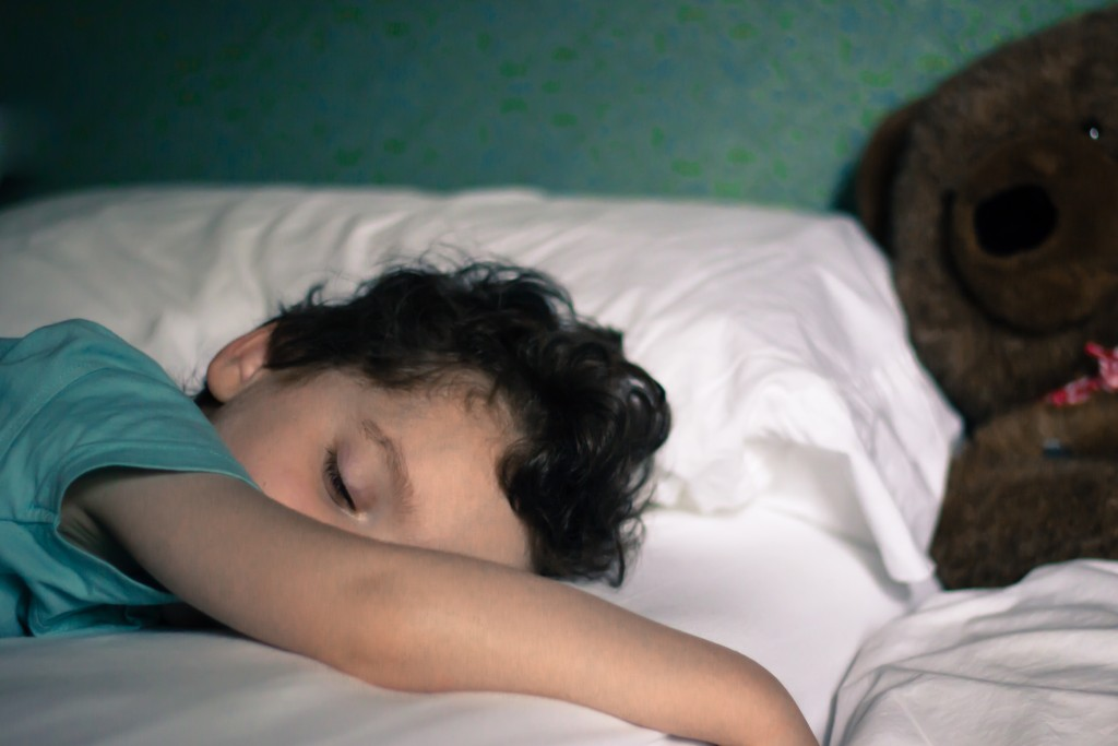 Young child sleeping in bed with teddy in background