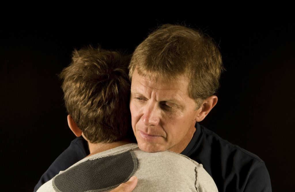 Sad embrace - father and son