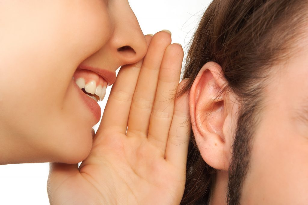 A women whispering in someone's ear while smiling