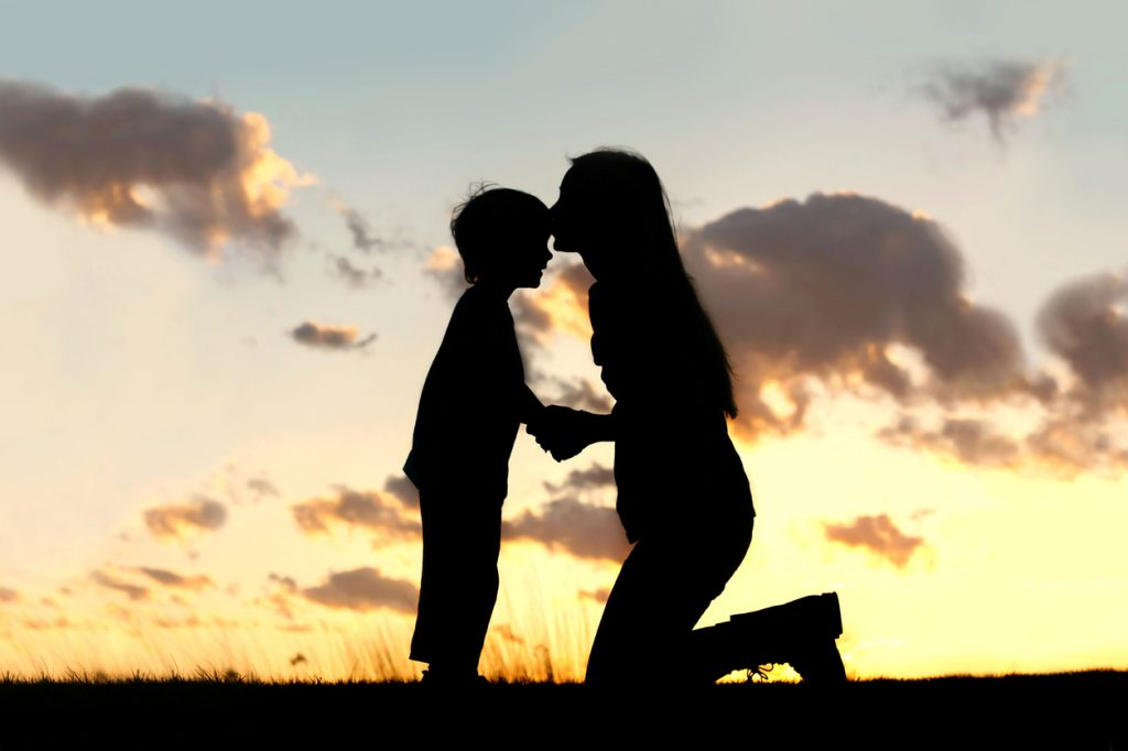 Mother Lovingly Kissing Little Child at Sunset
