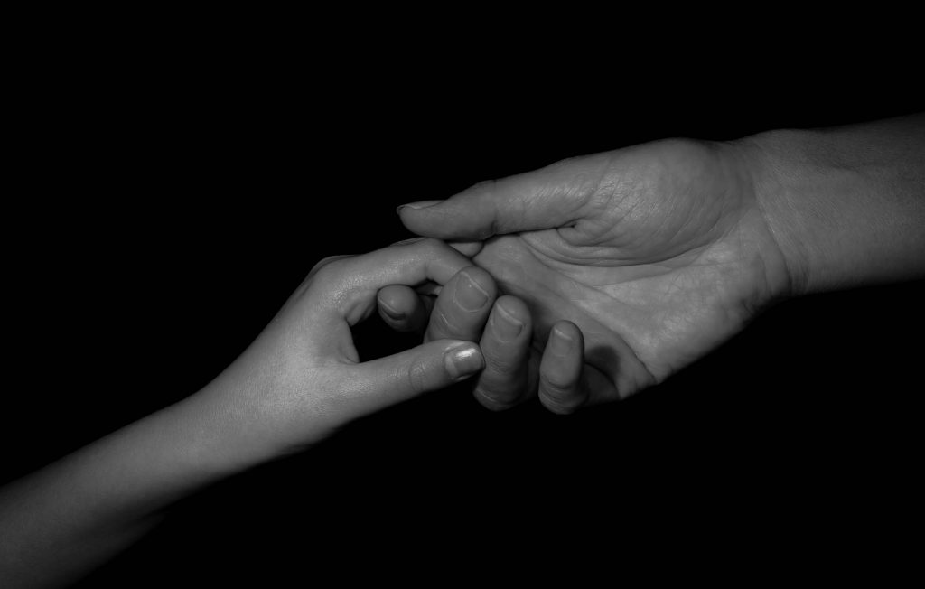 mother holding child's hand, black and white image.